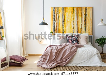 Yellow monochromatic painting above a big double bed #671163577