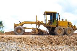 Yellow Motor grader (Road grader) working at road construction site.