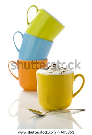 yellow mug filled with cappuccino, spoon in front, green, orange and blue mugs stacked in background, on white reflective surface