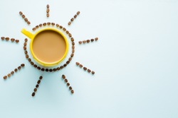 Yellow mug of coffee with milk on light pastel blue table from above. Wake up with morning coffee. Sun created from brown beans. Empty place for inspirational, motivational text or quote.  Top view.