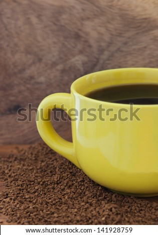 Yellow mug with coffee on the table with a instant coffee granules and wooden board background