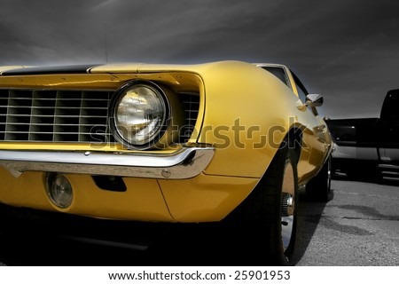 Yellow muscle car against dark cloudy background