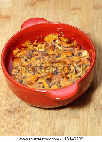 yellow mushrooms ( cantharellus cibarius ) left in water in a red bowl