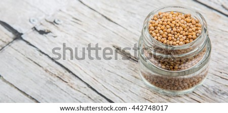 Yellow mustard seed in mason jar over wooden background