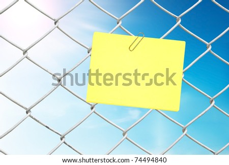 yellow note on chain link fence see blue sky