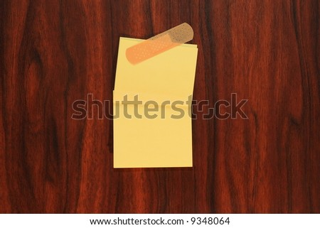 Yellow note paper with bandage on the door