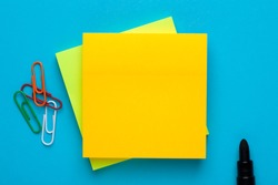 Yellow note with empty place for your text with marker and paper clips on blue background. Reminder concept.