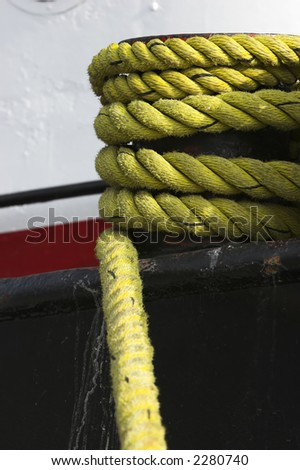 Yellow nylon rope holding a ship to a dock