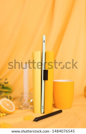 yellow objects on a yellow background: books, tablet, cup, pen. stand upright #1484076545