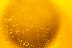 Yellow oil bubbles on water, cooking oil background.