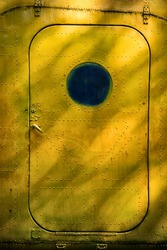 Yellow old door from an airplane with round glass.