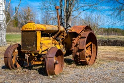 yellow old tractor with iron wheels