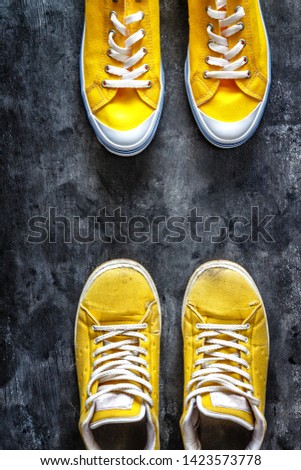 yellow old worn dirty torn sneakers and and new sneakers on a dark grunge background. top view. Copy space