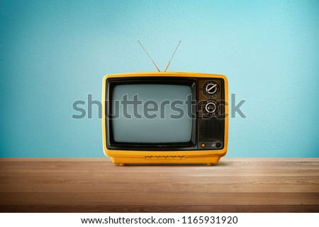 Yellow Orange color old vintage retro Television on wood table with mint blue background .