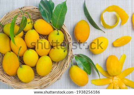 Yellow-orange fruits in a wicker basket and with a camparine around the background of the cloth. Stok fotoğraf ©