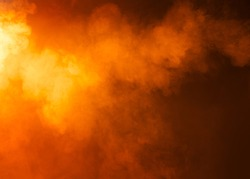 Yellow/Orange mysterious fog photographed on a black background. Ideas as a background texture or overlay. Bright light coming from the left of the image.