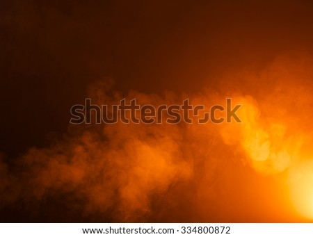 Yellow/Orange mysterious fog photographed on a black background. Ideas as a background texture or overlay. Bright light coming from the bottom right of the image.