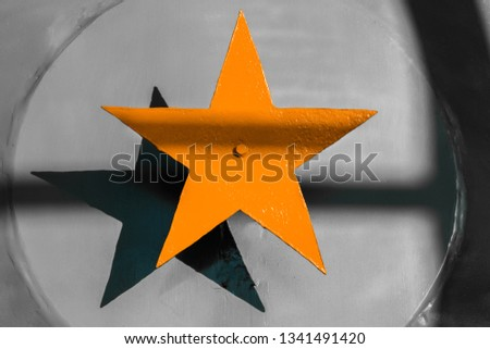 Yellow orange steel five-pointed star on a gray metallic background