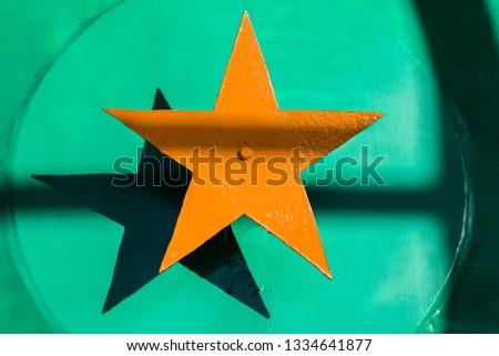 Yellow orange steel five-pointed star on a green metallic background