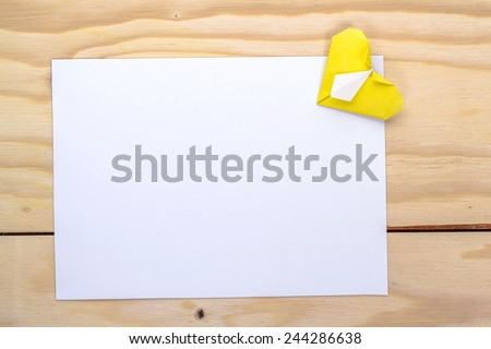 yellow origami heart and white paper sheet for romantic letter.