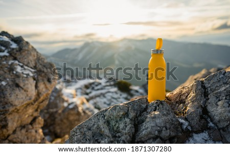 Yellow outdoor travel water bottle. Male hand holding bottle. Mountains and winter in national park in during sunset. Travel concept, drink water, adventure