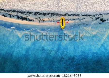 Yellow packraft rubber boat with red padle and turquoise water waves from top view. Beach with yellow sand glowing by sunlight. Travel summer vacations seascape background from drone Stock fotó ©