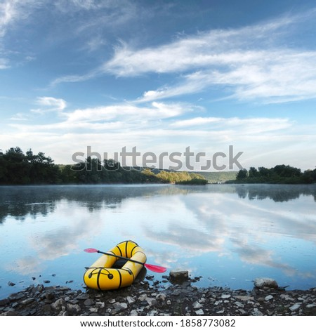 Yellow packraft rubber boat with red padle on a sunrise river. Packrafting. Active lifestile concept Stock fotó ©