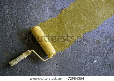 Yellow paint roller on concrete background
