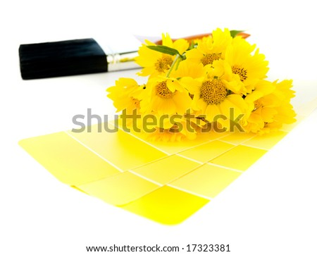 Yellow paint sample swatches and wild yellow sunflowers with a paintbrush in the background isolated on white.