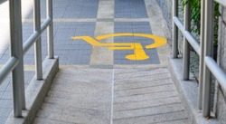 Yellow painted handicapped sign traffic symbol on the floor in front of ramp way for support wheelchair