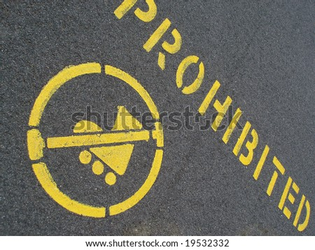 yellow painted pavement sign prohibiting inline skating
