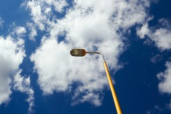 yellow painted street lamp on a background of blue sky with white clouds