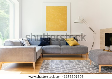 Yellow painting and lamp in modern living room interior with grey corner sofa. Real photo #1153309303