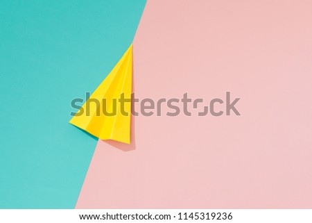 Yellow paper airplane on pastel pink and blue background. Minimal flat lay school concept. #1145319236