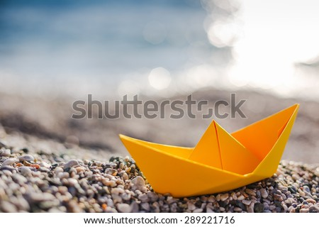 Yellow paper boat on beach on sunset time