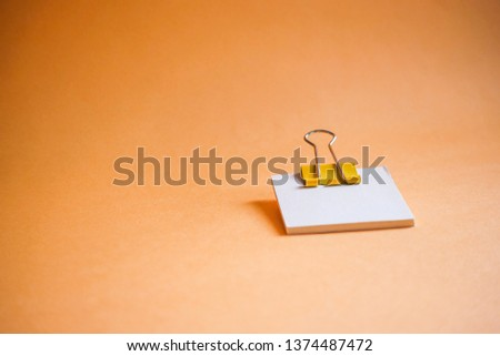 Yellow paper clip and blank paper on a orange background #1374487472