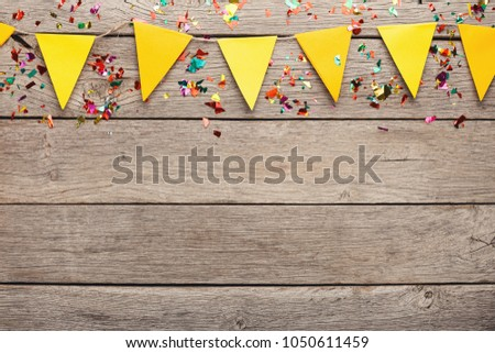Yellow paper flags garland on rustic wood. Birthday party decoration background, top view, copy space. Mockup for greeting card