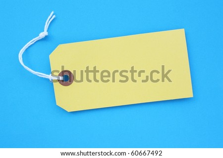 Yellow paper luggage tag with copy space on blue background
