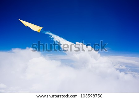 Yellow paper plane flying over clouds against blue sky