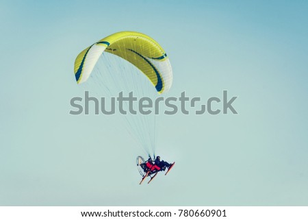yellow paraglide flying over clear blue winter sky. paraglider with a passenger. Adventure man active extreme sports pilot flying in the sky with paramotor paraglider paraglider motor. #780660901