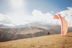 Yellow paraglider in high mountain cloudy sky. Hillside Hillside paragliding. Tourism, vacation concept