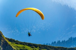 Yellow paraglider over the Green Mountain slope. Paraglider fly over mountain slope on sunny summer day,