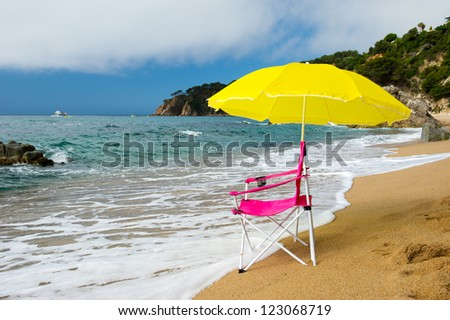 yellow parasol and pink chair for relaxing at the summer beach - stock photo