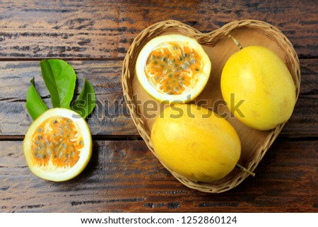 yellow passion fruit and passion fruit cut in half in heart-shaped basket on wooden table.Top view