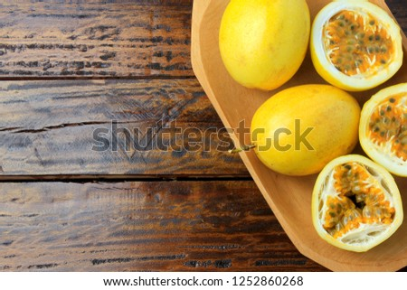 yellow passion fruit and passion fruit cut in half in wooden bowl on wooden table. free space for text