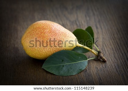 Yellow pear lying on a dark brown table. - stock photo
