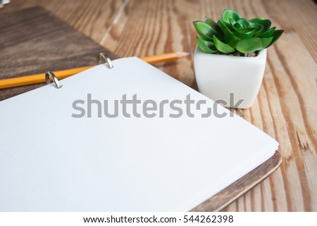 Yellow pencil and note book with plant on wood background
