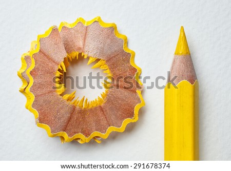yellow pencil and shavings on white paper background