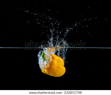 yellow pepper falling and splashing into water.