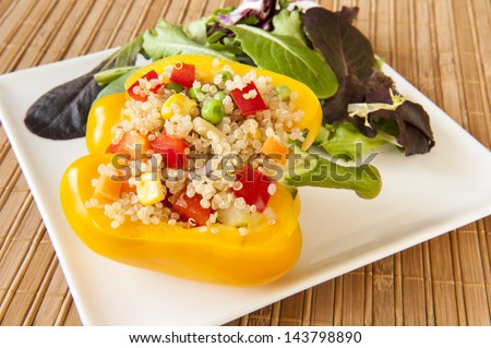 Yellow pepper stuffed with quinoa and mixed vegetables with green salad